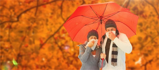 man and woman under umbrella with head colds sneezing into handkercheif