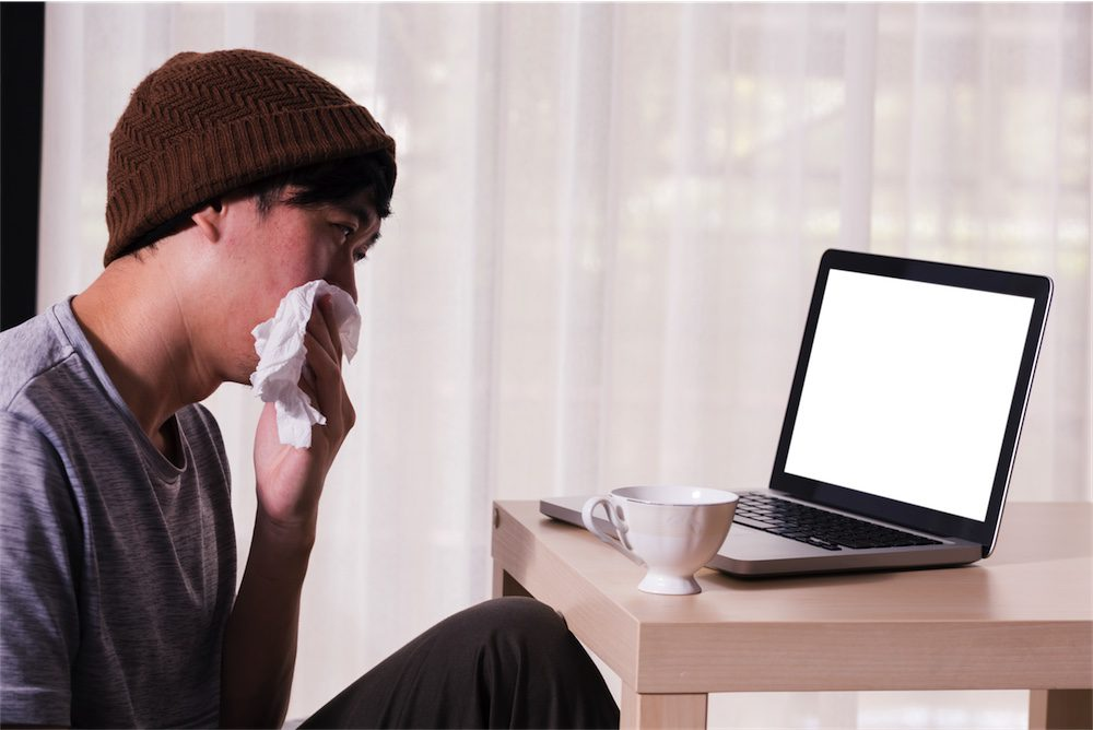 young man with head cold on naturoapth telehealth appointment
