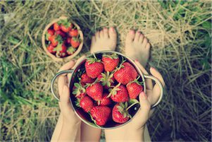 Naturopath holding a bowl of strawberries