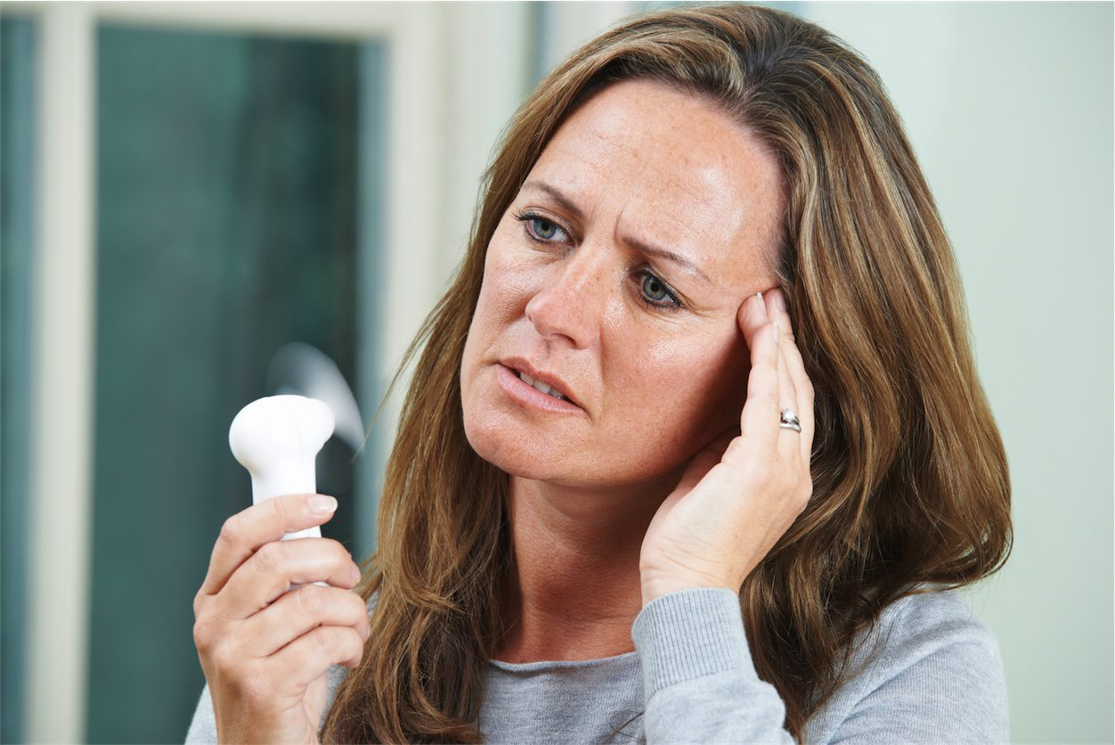 menopause woman using a fan to naturally treat hot flushes