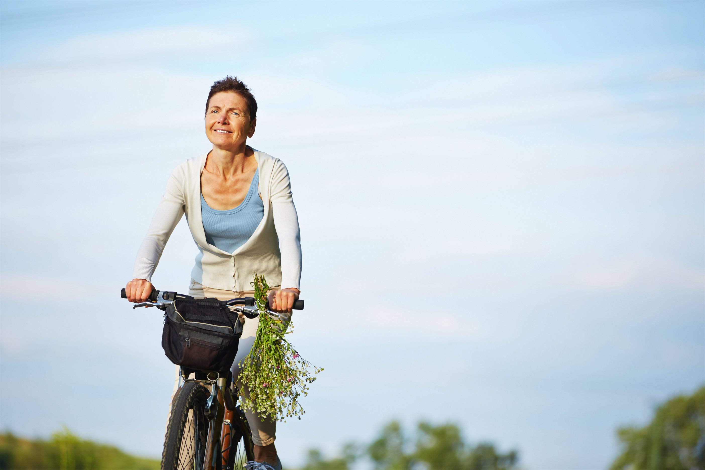Healthy menopause woman riding bike in nature